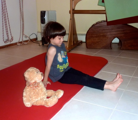 Sammy sits with the teddy from Watch Me Do Yoga